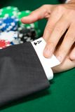 Poker player cheats with card from the sleeve Stock Images