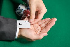 Poker player cheats with playing card from the sleeve Royalty Free Stock Photography
