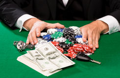 Poker player with chips and money at casino table Stock Images