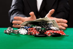 Poker player with chips and money at casino table Royalty Free Stock Photos