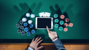 Poker player with digital tablet royalty free stock image