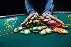 Poker player going all in pushing his chips forward Royalty Free Stock Photos