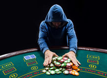 Poker player going all-in pushing his chips forward Royalty Free Stock Images