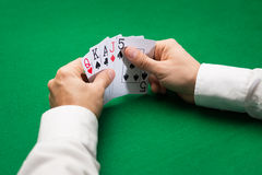 Poker player holding playing cards at casino table. Casino, gambling, poker, people and entertainment concept - close up of poker player holding playing cards at Stock Photo