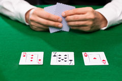 Poker player holding playing cards at casino table. Casino, gambling, poker, people and entertainment concept - close up of poker player holding playing cards at Royalty Free Stock Photography