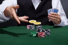 Poker player increasing his stakes. Throwing tokens onto the gaming table to meet or beat his opponents wager to stay in the game Royalty Free Stock Photography