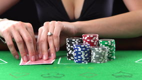 Poker player looking at her cards and goes all-in. Concept of gambling, risk, luck, win, fun, and entertainment. Prores. Poker player goes all-in and puts her stock video