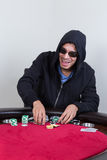 Poker player rakes in chips and starts to stack them. While smiling Stock Photo