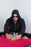 Poker player rakes in winning chips. While looking at the camera Stock Image