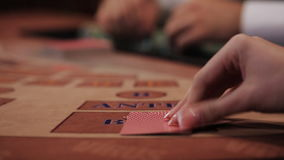 POKER: The player's hand opens and looks his cards on a table. Stack of chips and two aces stock footage