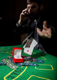 Poker player showing a losing combination in a poker cards, man drinks whiskey from grief.  Royalty Free Stock Photo