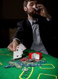 Poker player showing a losing combination in a poker cards, man drinks whiskey from grief.  Stock Photo