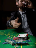 Poker player showing a losing combination in a poker cards, man drinks whiskey from grief.  Royalty Free Stock Image