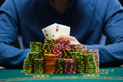 Poker player showing a pair of aces. Closeup. Poker player sitting at a poker table with chips and showing a pair of aces. Closeup royalty free stock image