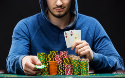 Poker player showing a pair of aces. Poker player sitting at a poker table with chips and showing a pair of aces. Closeup royalty free stock photo