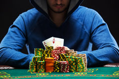 Poker player showing a pair of aces. Poker player sitting at a poker table with chips and showing a pair of aces. Closeup royalty free stock image