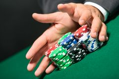 Poker player stakes. All in pushing his chips forward. Risky entertainment of gambling Stock Images