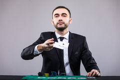 Poker player in suit throwing two ace cards. Royalty Free Stock Photos