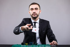 Poker player in suit throwing two ace cards. Poker player, on a grey background, throwing two ace cards Royalty Free Stock Photo