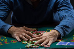 Poker player taking poker chips after winning Royalty Free Stock Images