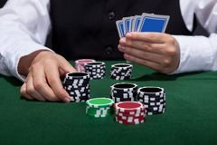 Poker player about to place a bet. Male poker player about to place a bet moving a stack of tokens towards the centre of the gaming table with his free hand Stock Photos