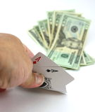 Poker player views pocket pair aces, cash bet Stock Photos