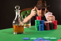 Poker player wearing sunglasses and hat Stock Photo