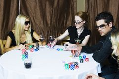 Poker players. Group of attractive young caucasians enjoying a glass of wine and playing poker Stock Photo