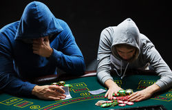 Poker players sitting at poker table and going all-in Stock Image