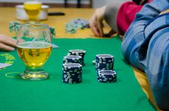 Poker chips with playing cards on a green table. Poker players with yours poker chips, having a beer. There are some blue chips and a glass of beer Stock Images