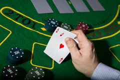 Poker playing card on a green table background, man holding two aces Royalty Free Stock Images