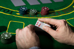 Poker playing card on a green table background, man holding two aces Royalty Free Stock Photo