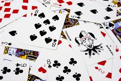 Poker Playing Cards. Scattered poker cards with joker centered in right portion of the frame stock photo
