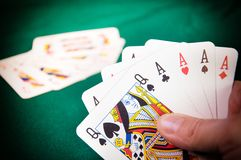 Poker in Hand. Poker. A queen and four aces in hand royalty free stock images