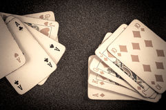 Poker royal straight flush and three of a kind vintage cards on a table background Royalty Free Stock Image