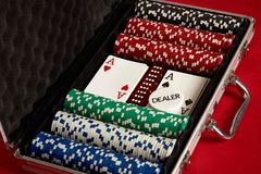 Poker set in metal suitcase. Risky entertainment of gambling. Top view on red background. Casino background. Copy space. Still life Stock Photos