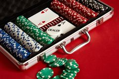 Poker set in metal suitcase. Risky entertainment of gambling. Top view on red background. Casino background. Copy space. Still life Royalty Free Stock Photos
