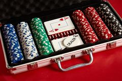 Poker set in metal suitcase. Risky entertainment of gambling. Top view on red background. Casino background. Copy space. Still life Royalty Free Stock Image
