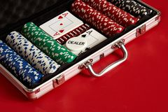 Poker set in metal suitcase. Risky entertainment of gambling. Top view on red background. Casino background. Copy space. Still life Stock Photo