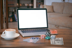 Poker set in a metallic case with laptop over wooden table, retro filtered image Stock Images