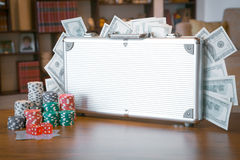 Poker set in a metallic case with lot of money over wooden table, retro filtered image Stock Image
