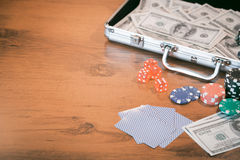 Poker set in a metallic case with lot of money over wooden table, retro filtered image Stock Images