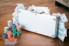 Poker set in a metallic case with lot of money over wooden table, retro filtered image Royalty Free Stock Photography