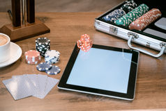 Poker set in a metallic case with tablet over wooden table, retro filtered image. Stack of old books and tablet over wooden table Stock Image