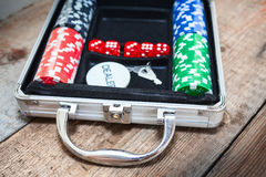 Poker set in metallic case on wooden floor Stock Photo