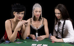 Poker table. Three attractive girls dressed in moulin rouge clothing playing cards at green poker table Royalty Free Stock Images
