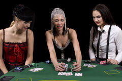 Poker table. Three attractive girls dressed in moulin rouge clothing playing cards at green poker table Stock Images