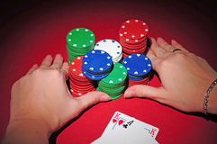 Poker table. All in. Poker player going all in pushing his chips on a red poker table Stock Photo