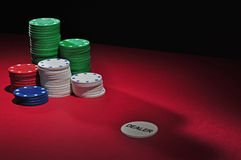 Poker table chips and dealer. Several stacks of casino chips of various heights and colors with a dealer chip, all sitting on a red colored playing surface. The royalty free stock photo