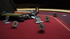 Poker table with poker chips in suitcase and falling on the table in casino. Poker chips for gambling card game.